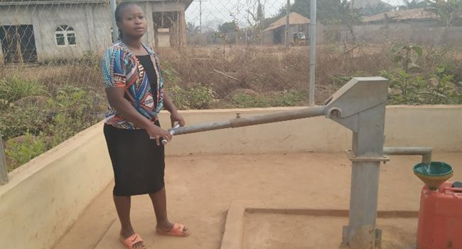 Ijeoma trying to get water from the borehole